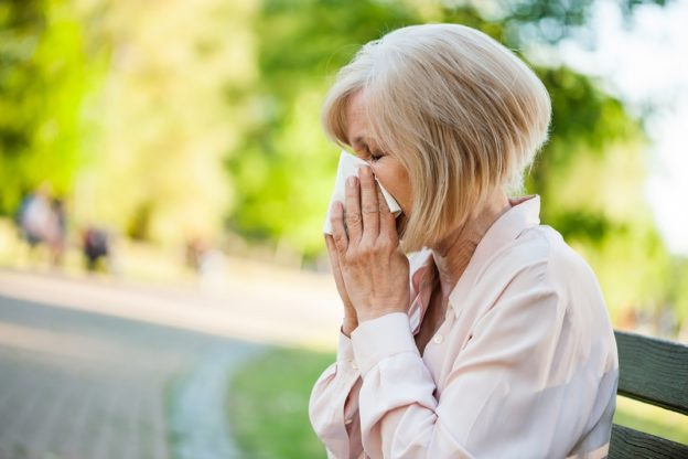 Woman with Allergies Outside Sneezing