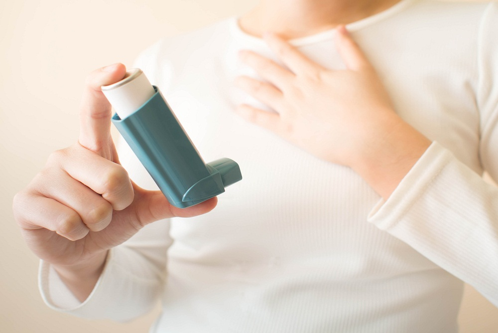 Female with asthma holding an inhaler