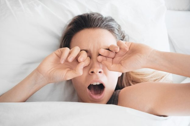 Woman in bed yawning and rubbing eyes