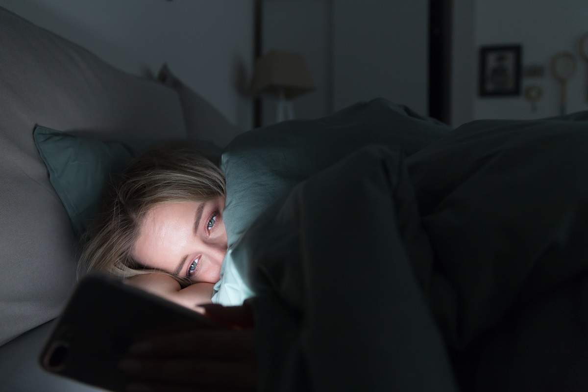 Woman looking at cellphone in bed