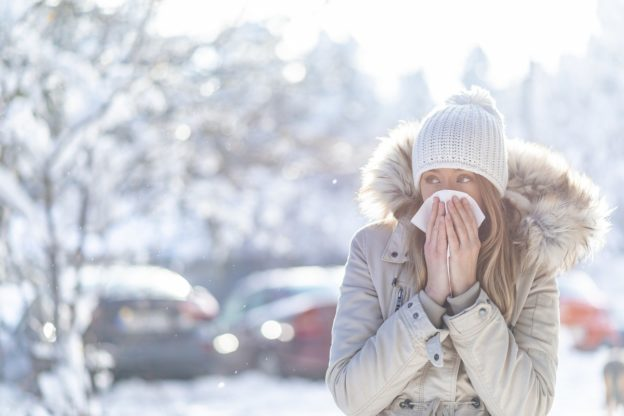 Woman blowing nose with snowy backdrop