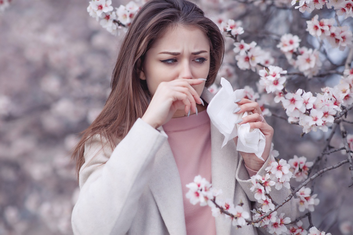 Woman next to flower blossoms wiping nose