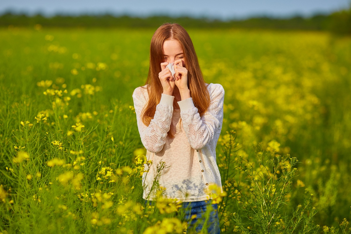 Woman blowing nose in field of flowers