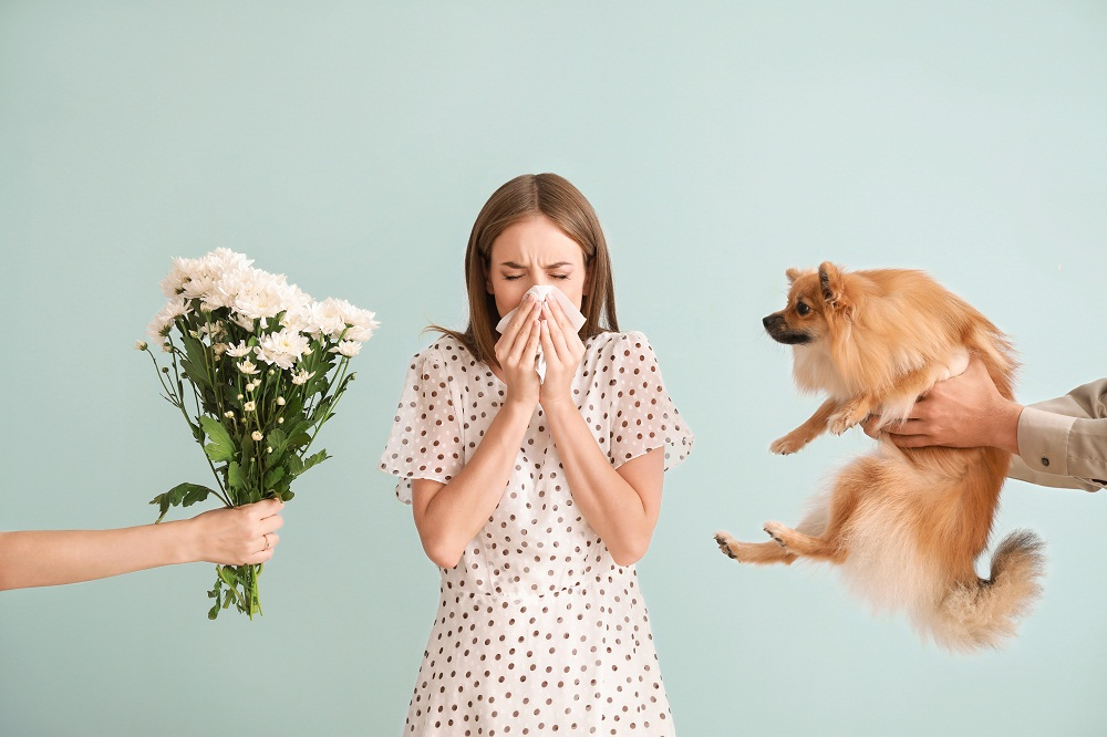 Lady Blowing Her Nose with Tissue and Standing in Middle of Two People Holding a Dog and Flowers on Each Side