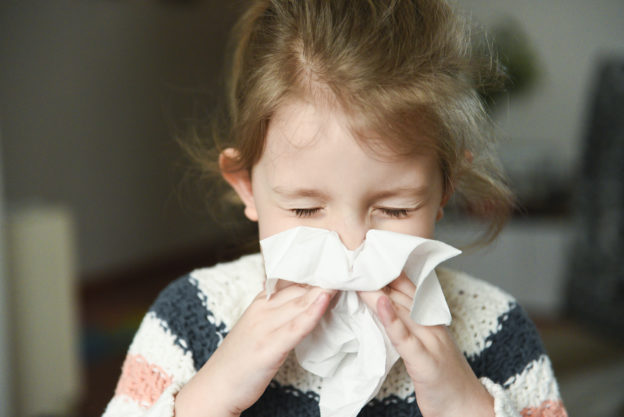 Little Girl with Allergies Blowing Nose with Tissue